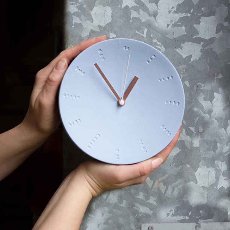 De rustige tinten van het porselein geven de moderne eigentijdse klok een zachte uitstraling. De uren- en minutenwijzers zijn warm koperkleurig.