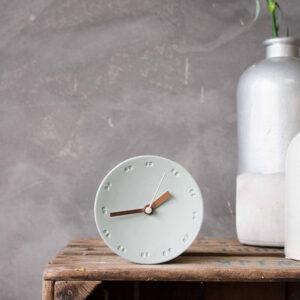 De eenvoud van het ontwerp maakt dat de porseleinen klok past in allerlei interieurs zoals ook op een wand met pure materialen.
