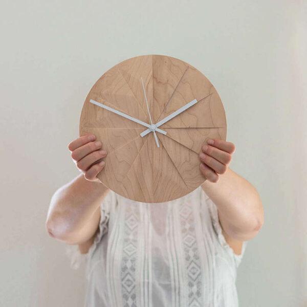 Ilse heeft de design klok Shady in haar handen. Je ziet de prachtige nerven in het hout van deze moderne klok met witte wijzers. Alt-tekst bewerken