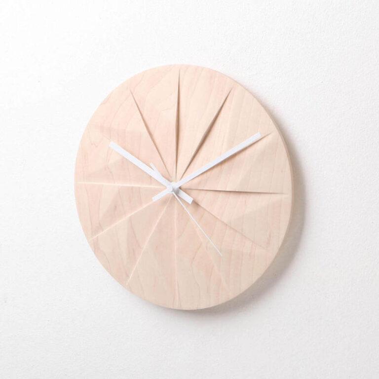 De licht houten Shady klok heeft witte wijzers en de wijzerplaat is in 12 vlakken verdeeld die de uren verbeelden. Design Pana Objects.