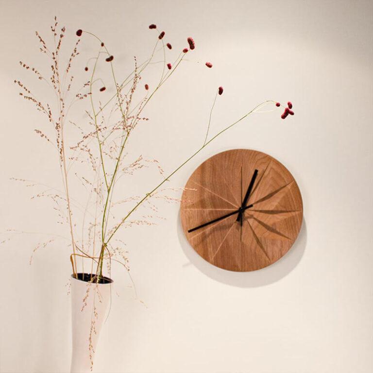 De naam van deze klok is 'Shady', het Engelse woord voor schaduw. Voor de uren zijn heel geraffineerd 12 vlakken uit de houten wijzerplaat gesneden.