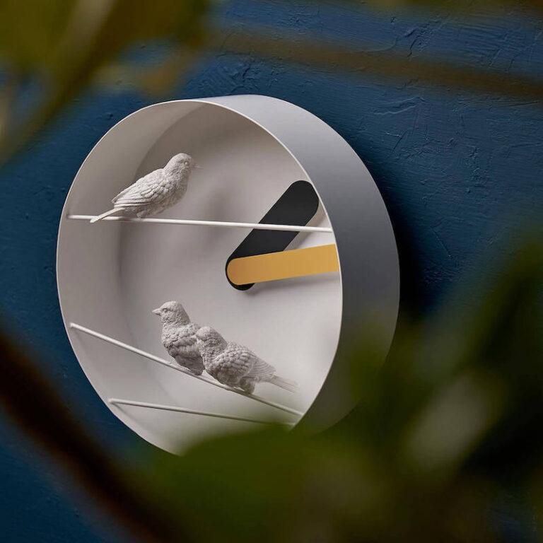 Hier zie je dat de Sparrow X klok 9 cm diep is en dat de 3 mussen voor de klok zijn geplaatst. Het is een prachtige modern witte design klok.