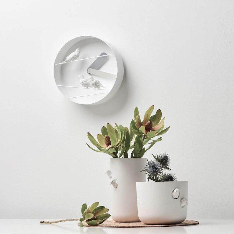 De Sparrow X klok is een witte moderne ronde klok waarbij 3 witte mussen voor het uurwerk op witte metalen draden zitten. Donker- en lichtgrijze wijzer.