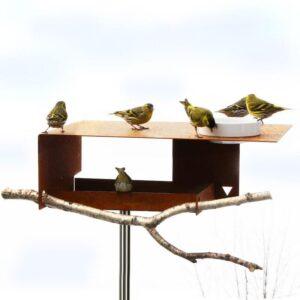 Je kunt het voer zowel op het dak als onder het grote dak van de vogelvilla Bauhaus strooien. Het porseleinen schaaltje gebruik je voor water of ook voor vogelvoer. Zoek zelf een mooie tak en steek die door de daarvoor gemaakte uitsparingen.