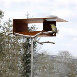 De Bauhaus vogelvilla met groot dak heeft een open karakter. Dat maakt het aanvliegen voor vogels gemakkelijk. Steek er zelf nog een mooie tak in waarop de vogels kunnen landen en uitrusten. Het porseleinen schaaltje hangt stevig in het dak.