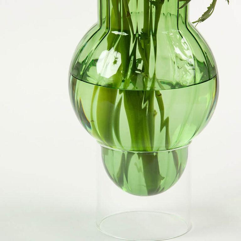 De moderne glazen Bubble Tube vaas van Studio About bestaat uit 2 delen. De groene vaas staat op een transparante glazen cilinder.