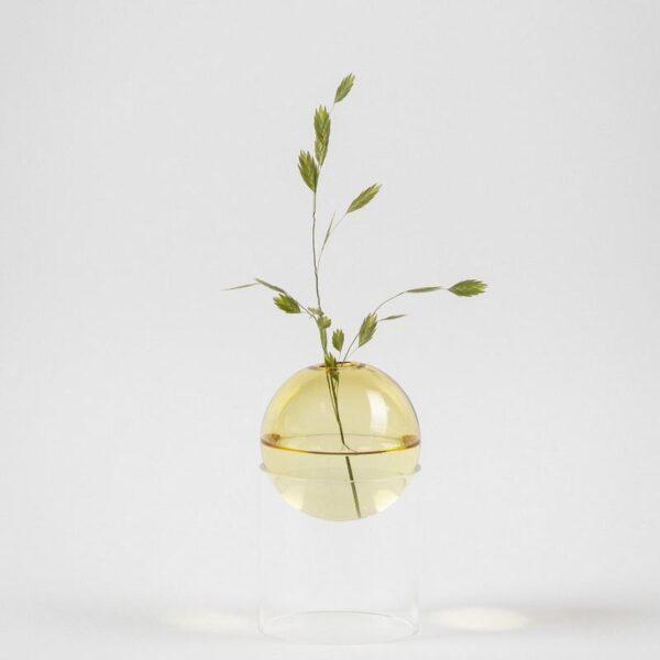 De gekleurde glazen bol van het Standing Bulb vaasje hangt in een transparant glazen sokkel. Dit geeft een subtiel zwevend effect.