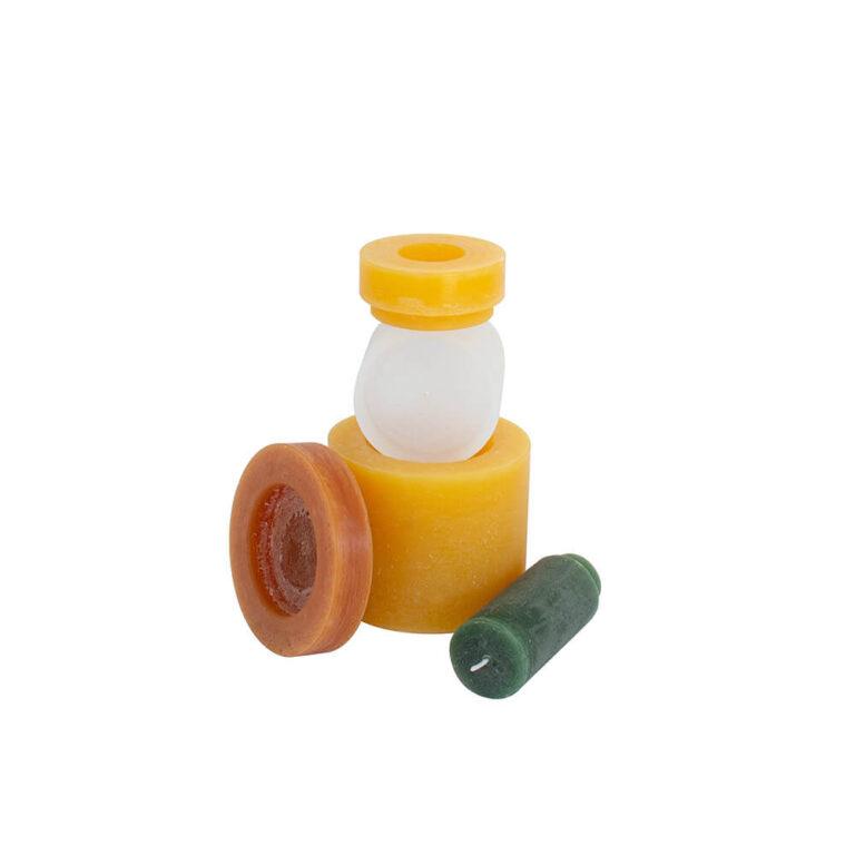 De Candl Stack 04 geel & groen bestaat uit 1 kaars in de kleur groen (de dunste en hoogste), een dikker exemplaar in wit en de aller dikste in een gele tint. De kleinste houder (zonder lont) is ook geel en de grootste is bruin.