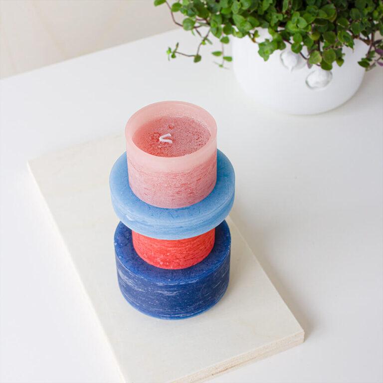 De Candl Stack Limited Edition in rood & blauw bestaat uit twee dikke kaarsen in de kleuren rood en roze, een dikker exemplaar in donkerblauw en een houder (zonder lont) in een lichter blauwe tint.