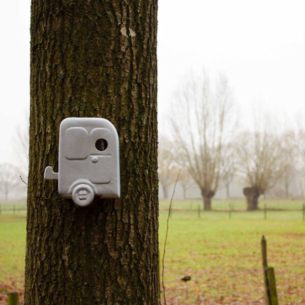 Dit nestkastje met de originele naam Trekvogel heeft de vorm van een typische ouderwetse Hollandse caravan. Hier opgehangen aan een boom. Handgemaakt in NL van winterhard steengoed.