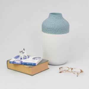 Door de toevoeging van de boeken naast de Clay vaas, krijg je een idee hoe groot de design vaas is. Dit is de uitvoering met een blauwe kraag.