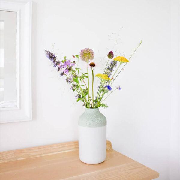 Door de smalle hals van de Clay vaas heb je maar weinig bloemen nodig voor een mooi arrangement, De zachtgroene bovenkant zorgt voor een mooie overgang van de bloemen naar de witte onderzijde.