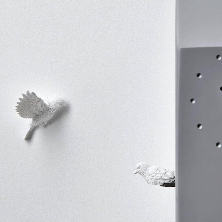 Elk uur komt er een koekoek uit de grijze Cuckoo klok van Hao Shi. Op de muur wacht een extra koekoek hem op. Moderne klok.