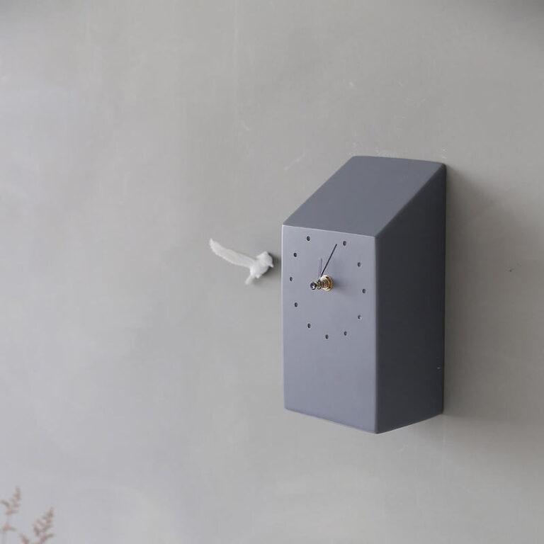 Het donkergrijze huisje van de Cuckoo klok is minimalistisch. Naast de moderne koekoeksklok vliegt een extra vogeltje op de wand.