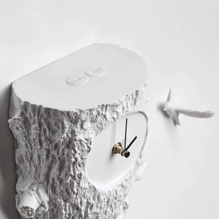 Geen huisje maar een witte boomstronk voor deze moderne koekoeksklok. Bovendien vliegt er een extra koekoek naast de klok op de wand.