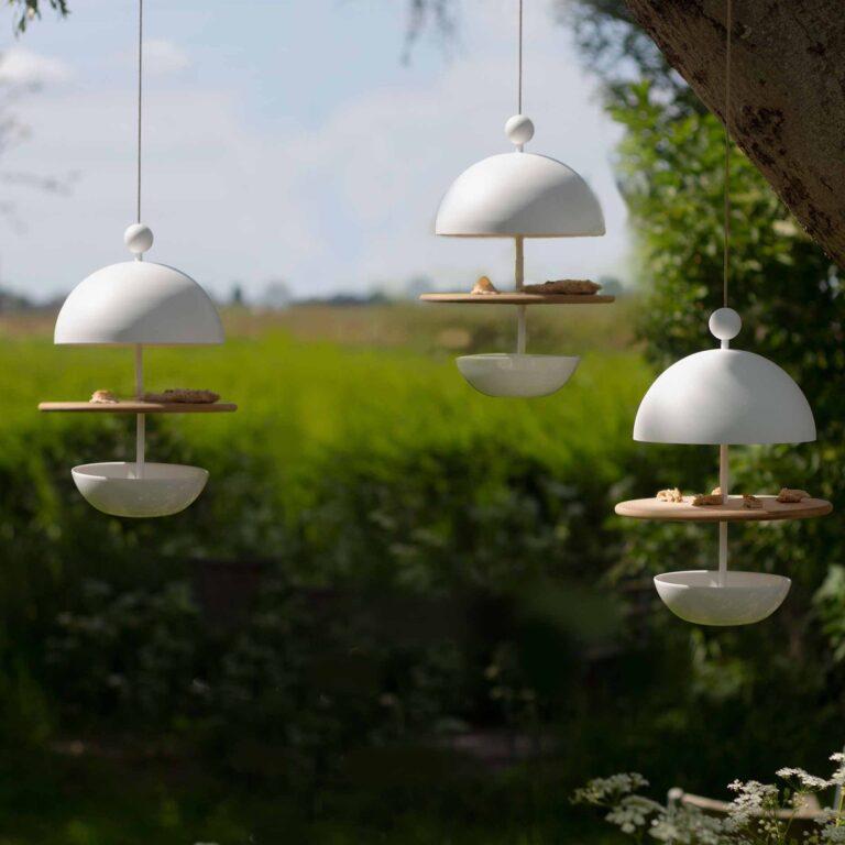 Het Dish of Desire vogelvoederstation heeft een wit aluminium frame met een plat bord van rood ceder hout en een diepe schaal van porselein. Er boven hangt een chique 'cloche' van aluminium. Hierdoor ontstaan er verdiepingen waardoor de vogeltjes en het voer droog blijven