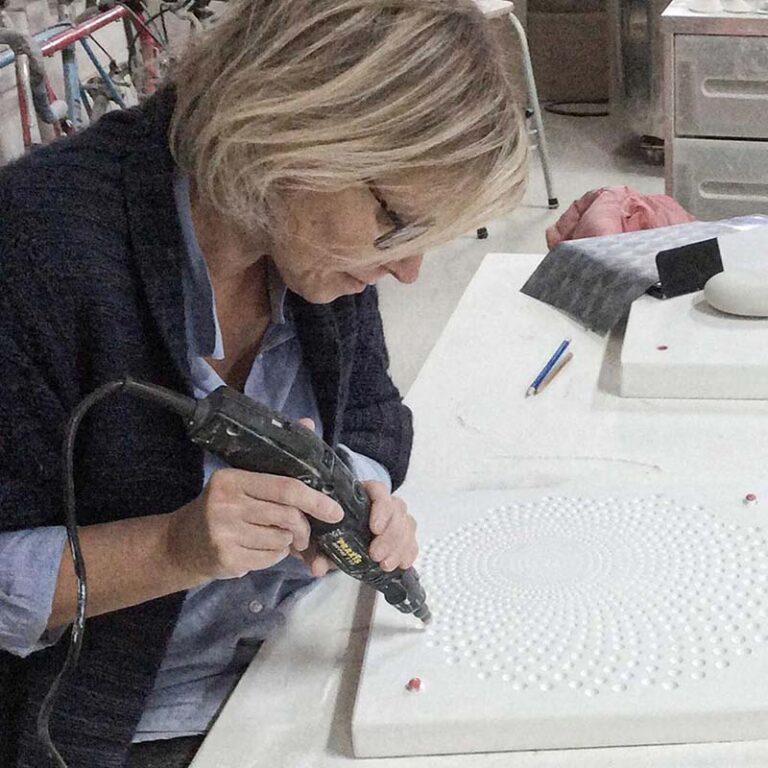 Jacqueline is gespecialiseerd in dessin ontwerp. Samen hebben ze gezocht naar een manier om vanuit het materiaal en de techniek van het gieten, de schalen een tweede huid te geven. Hier zie je haar bezig met het maken van het dessin in de mal.