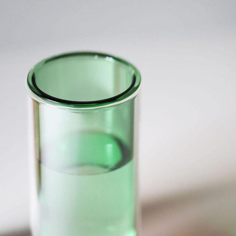 Zij-aanzicht van de Flower Tube design vaas. De gekleurde binnenvaas hangt in een transparante glazen cilinder.