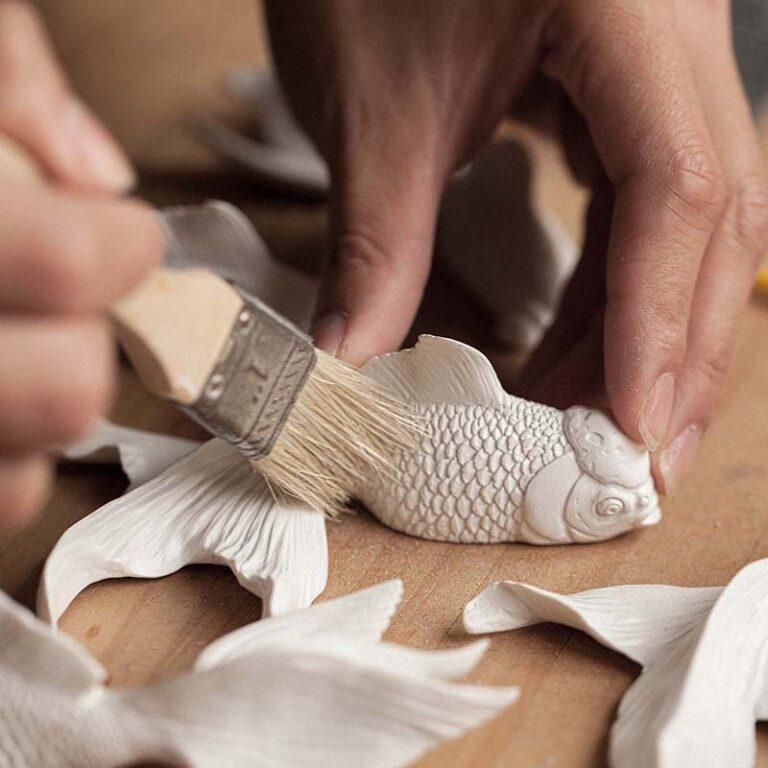 Als de schubben van de Goldfish klok zijn uitgewerkt wordt nauwkeurig het stof verwijderd.