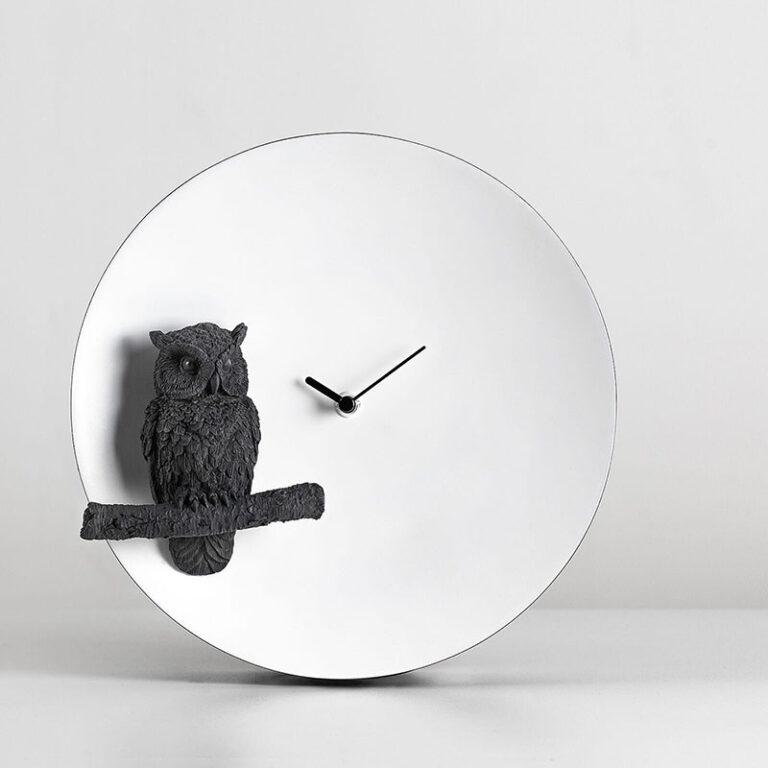 Een zwarte uil gemaakt in 3D op een tak voor de witte ronde klok zit die de maan verbeeldt. Zwarte wijzers geven de tijd aan.