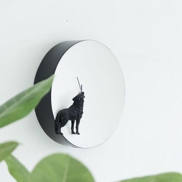Op de Moon klok Wolf zie je een zwarte wolf (3D) die naar de volle witte maan (de klok) huilt. De wolf is linksonder voor het uurwerk geplaatst.