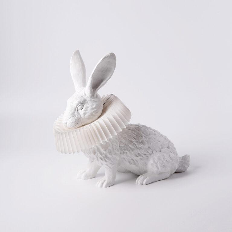 De Rabbit X is een moderne lamp waarbij het licht uit de papieren kraag komt die om de hals van een tot in detail uitgewerkt laag zittend konijn zit.