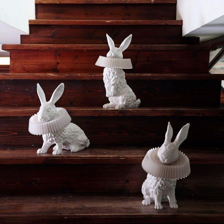 Op de trap staan de 3 verschillende Rabbit X design lampen: een hoog en laag zittend konijn en een versie met het konijn op zijn achterpoten.