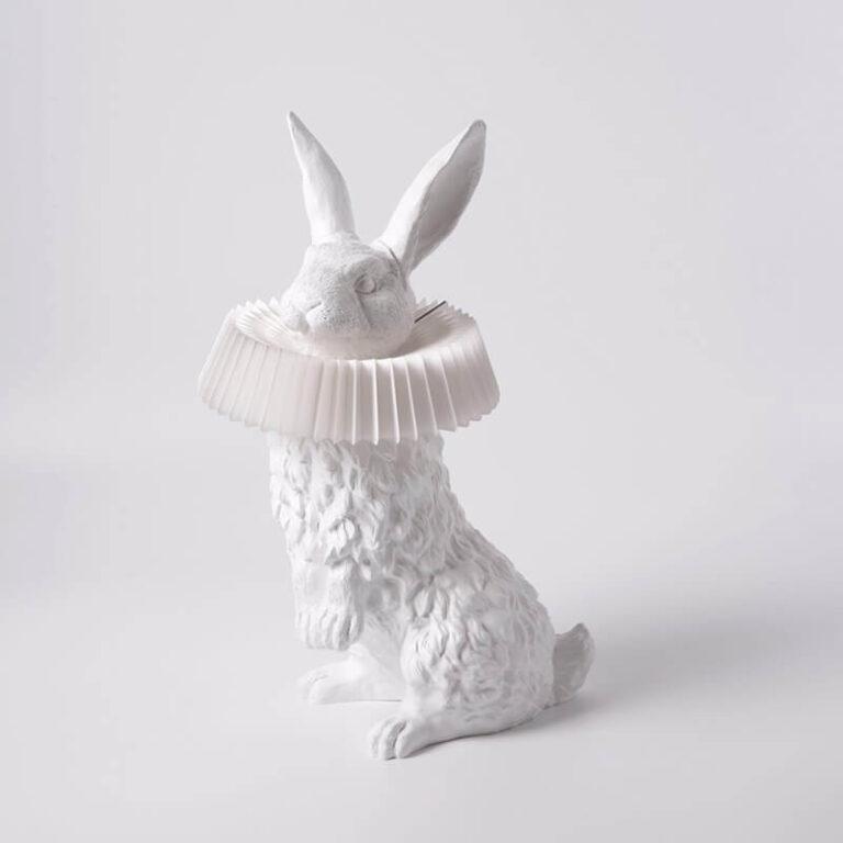 De Rabbit X is een moderne lamp waarbij het licht uit de papieren kraag komt die om de hals van een tot in detail uitgewerkt op zijn achterpoten staande konijn zit.