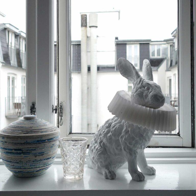Op een witte vensterbank met witte accessoires steelt de witte Rabbit X lamp nog steeds de show. Konijn met prachtige kraag om zijn hals.