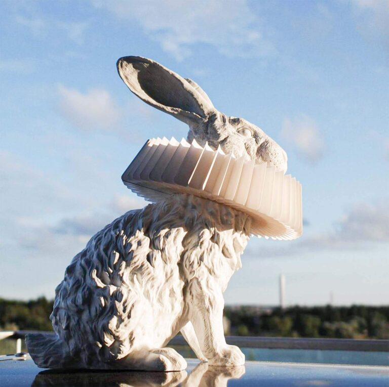 Rabbit X lamp van de zijkant gezien zittend op een vensterbank kijkt hij naar de mooie blauwe lucht buiten. Alle details van het dier zijn prachtig uitgewerkt in de witte kunsthars.