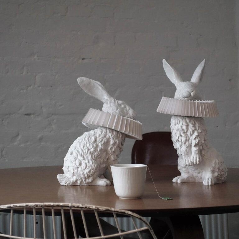 Op tafel zitten 2 konijnen van de Rabbit X design lampen: eentje op zijn achterpoten en een hoog zittend. Om hun halzen een prachtige 'gouden eeuw kraag'.