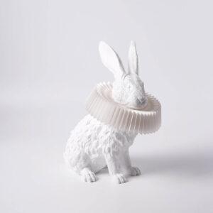 De Rabbit X lamp zitten vanaf de zijkant gezien. Het konijn en zijn kraag zijn beiden wit.