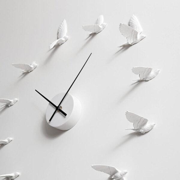 De 12 losse witte zwaluwen van de Swallow X klok lijken in westelijke richting te vliegen. Elke zwaluw is anders. Wit uurwerk met zwarte wijzers