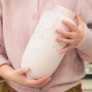 Ontwerpster Elke met in haar handen een porseleinen design vaas. Hierop heeft ze met de hand gestileerde veldbloemen getekend.