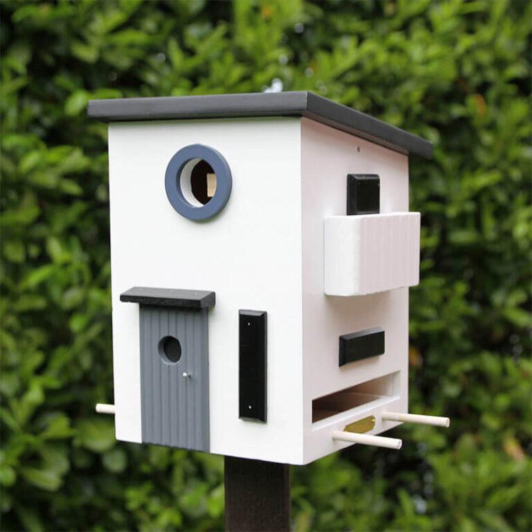 Vogellandhuis Bauhaus is gemaakt van hout. Het ronde raam is de ingang van het nestkastje. Dit sluit je in de winter zodat je de villa met vogelvoer kunt vullen. De vogels kunnen in de winter aan de zijkant op de stokjes zitten om hun buikjes vol te eten.