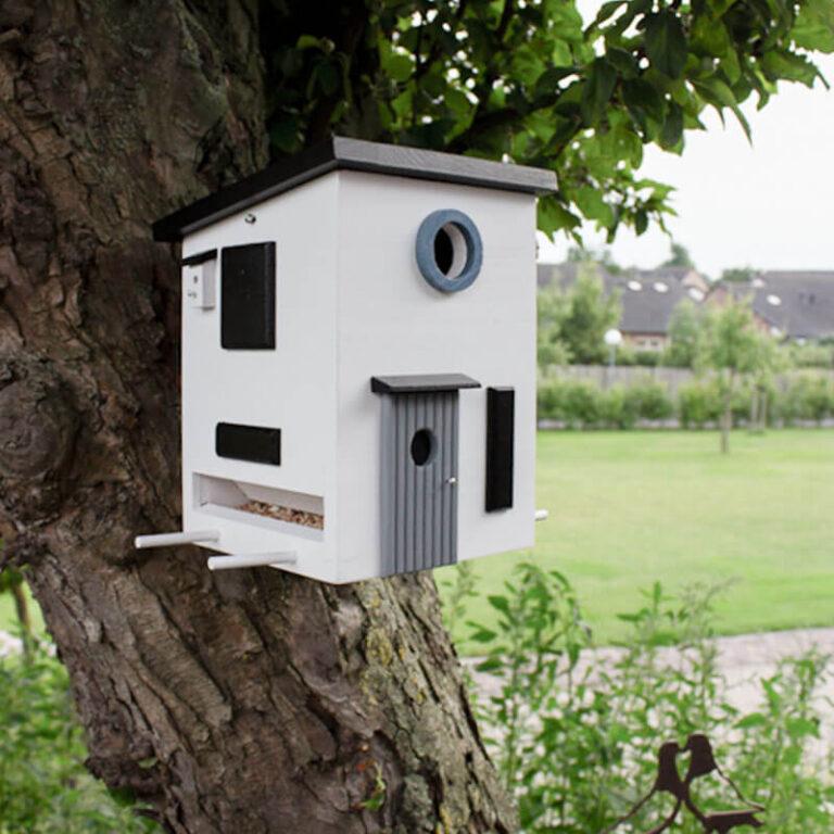 Dit houten vogelhuis in Bauhaus stijl heeft vele mooie details. Aan deze zijde zie je zelfs ter decoratie een piepklein nestkastje hangen. Een vogelhuisje op een vogelhuisje dus.