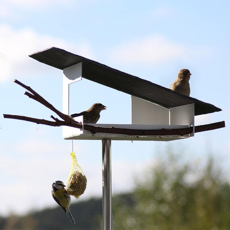 Het metaal van vogelhuis Leisteen is omgezet zodat je er zaden in kunt strooien. Voeg een tak toe als landings- en rustplaats voor de vogels.