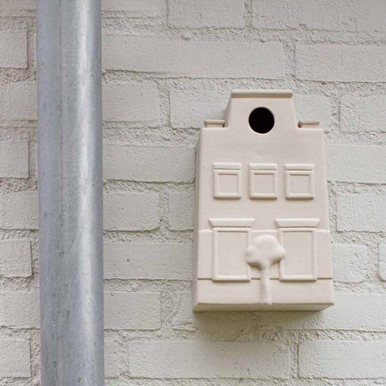 Voor het Hollandse vogelhuisje staat een boom. De vogels kunnen via het zolderraampje naar binnen. Gemaakt van steengoed bij Cor Unum. Zelfs op een witte muur is het een opvallende verschijning.