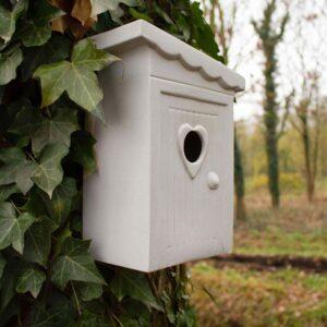 Dit nestkasje heeft de originele naam 'Schijtlijstertje'. Het is dan ook een modern vogelhuisje in de vorm van een ouderwets toilethokje. Hier opgehangen aan een boom. Handgemaakt in NL van winterhard steengoed.
