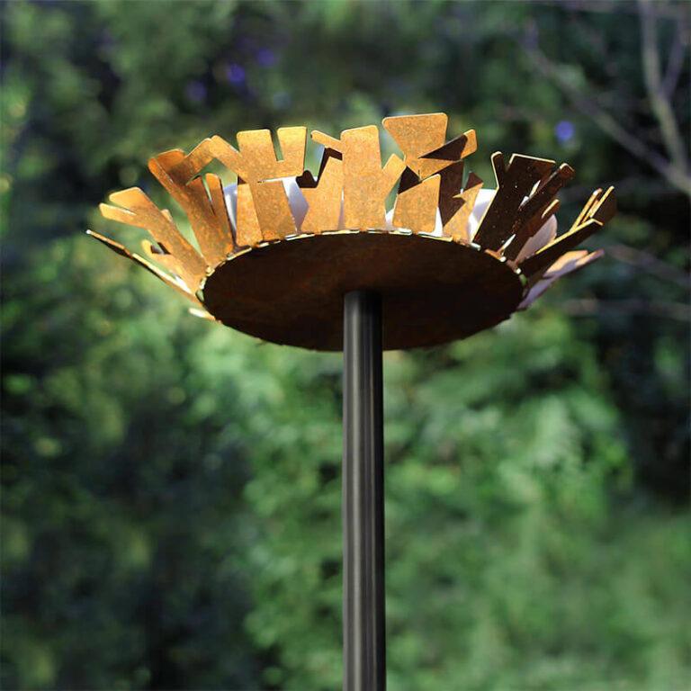 Het Nest vogelvoederstation is gemaakt van Cortenstaal. Hier zie de onderkant. De opstaande metalen rand stellen de takken voor waaruit een vogelnest normaal bestaat. Het cortenstaal wordt door weersinvloeden steeds mooier.