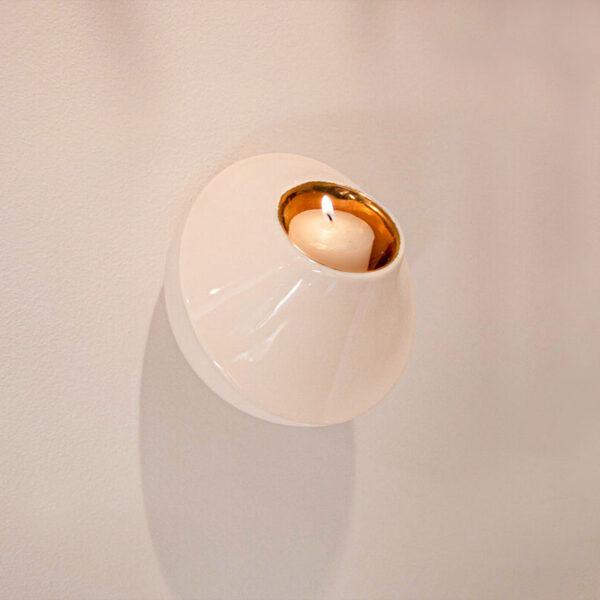 Wall light is een moderne waxinelichthouder voor aan de wand. De onderzijde is mat wit, de bovenzijde heeft een glanzende zandkleur. De binnenzijde is glanzend goud.