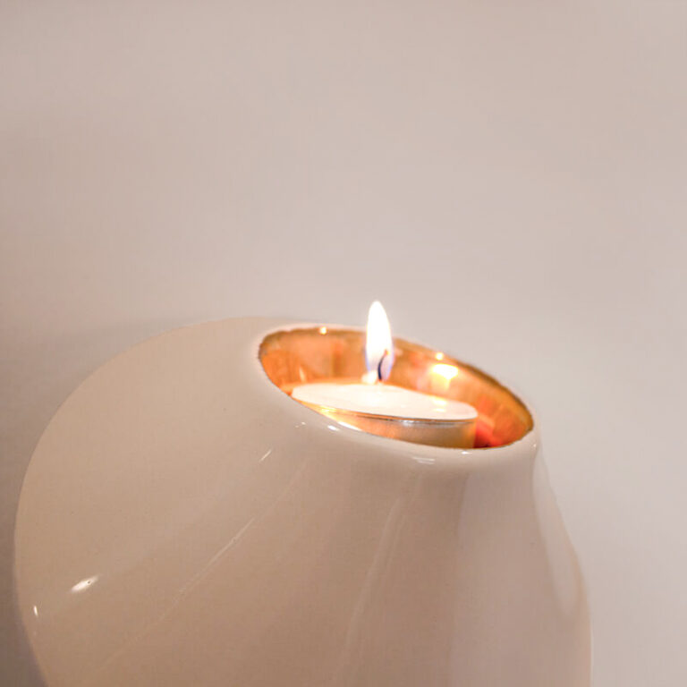 Aan de binnenkant is een gouden glazuurlaag aangebracht. Steek het waxinelichtje aan en je ziet direct dat dit de schittering het kaarslicht versterkt.