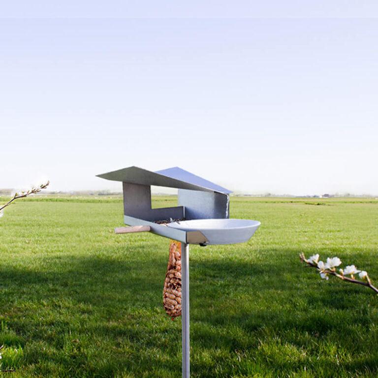 De Waterloop vogelvilla is gemaakt van RVS. Roest dus niet. Het voederstation staat op een hoge poot. Het architectonisch gevormde dak leidt regenwater naar het porseleinen schaaltje. Vogels kunnen uitrusten op het beukenhouten stokje.