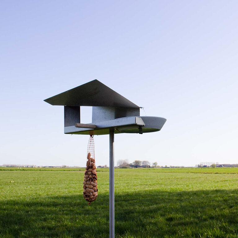 Door de 2 uitsparingen van de Waterloop vogelvilla steekt een mooie houten stokje. Vogels voelen zich daar direct op thuis. Aan de villa kun je eventueel nog een vetbol hangen.